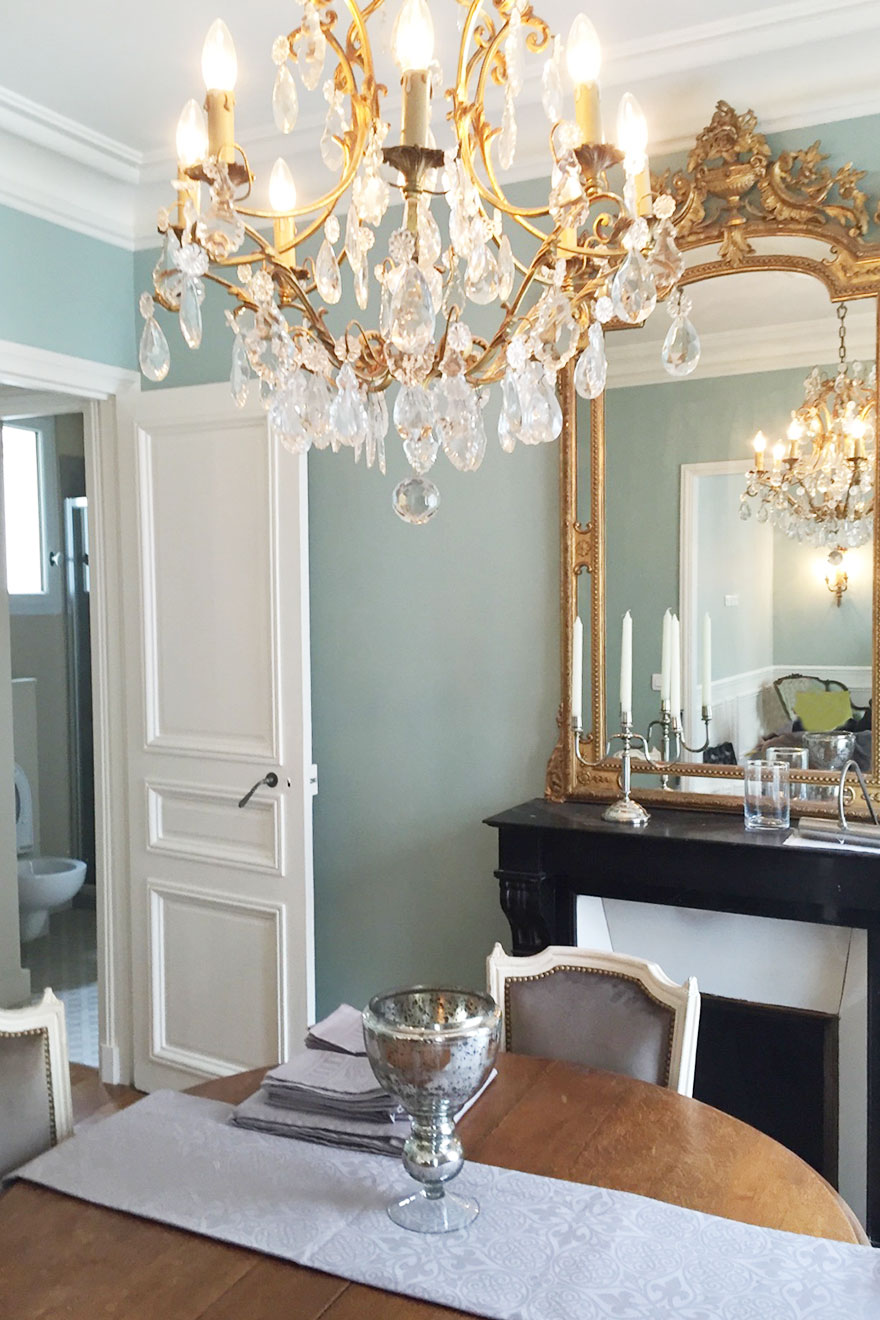 Stunning chandelier hangs over the dining table in the Bourgogne Paris Perfect rental