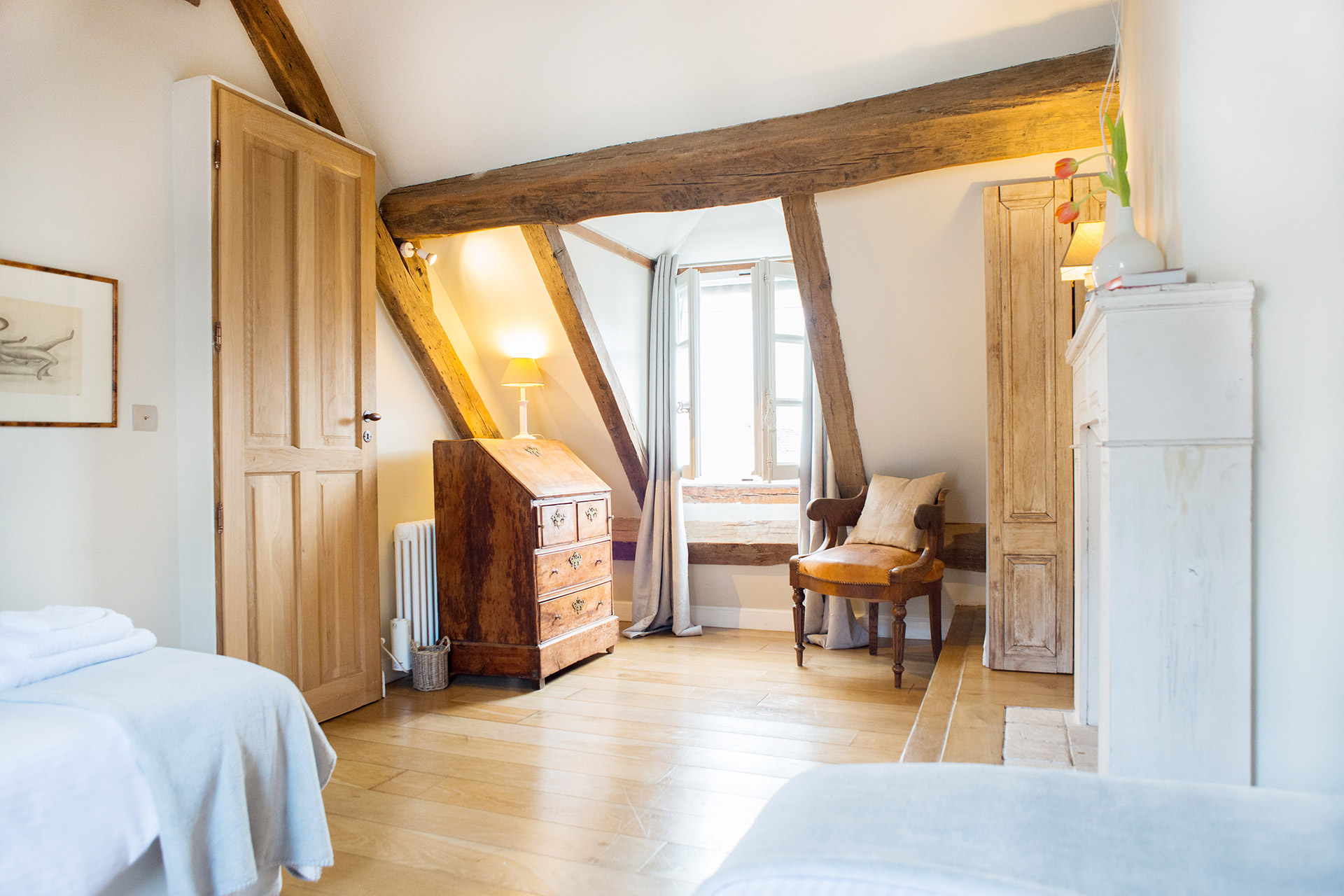 Slanting ceiling and exposed oak beams of the Brittany vacation rental offered by Paris Perfect