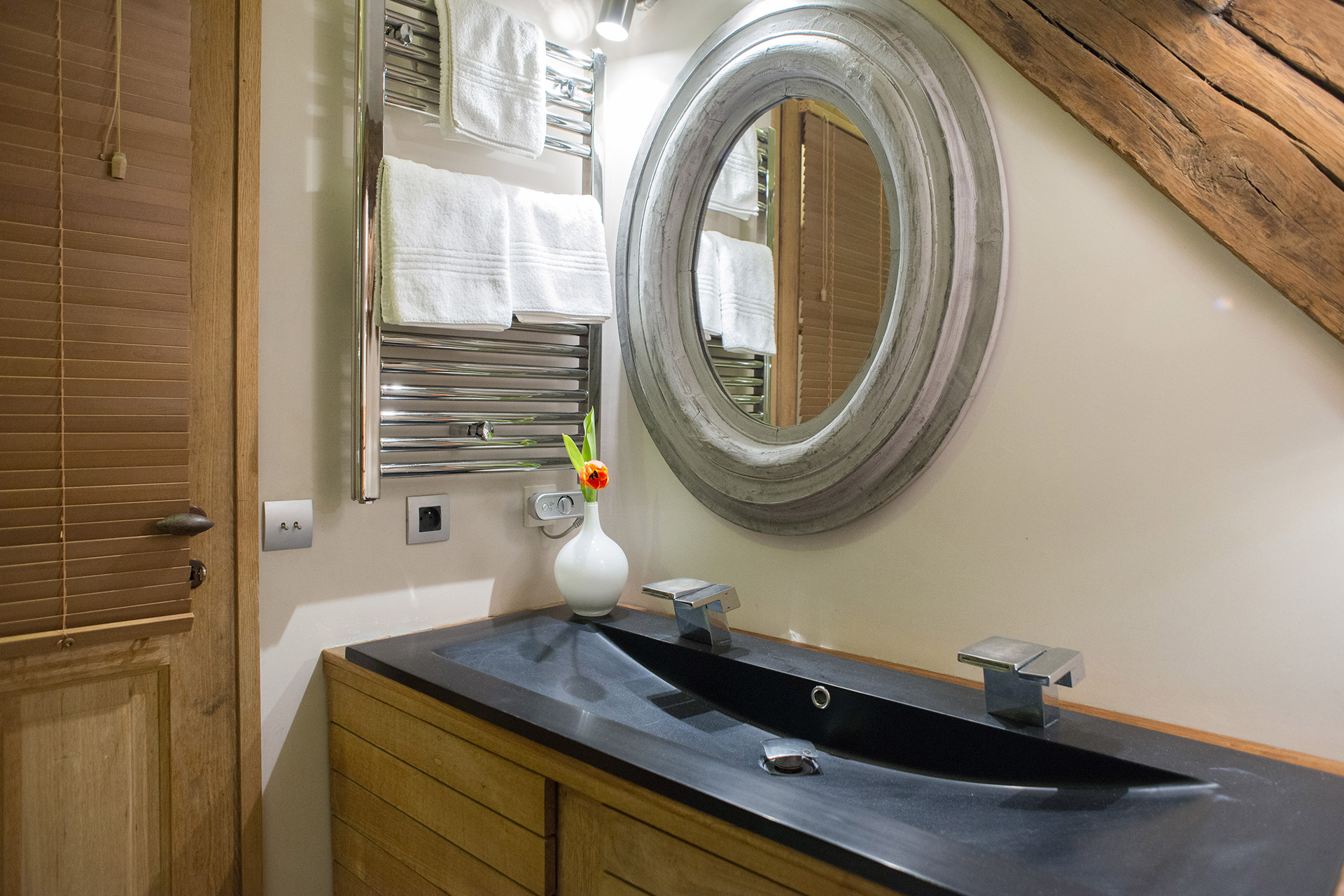 Bathroom with flexible showerhead and double sink in the Brittany vacation rental offered by Paris Perfect