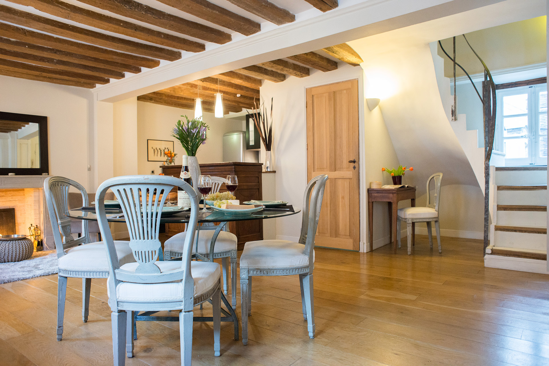 The living, dining, and kitchen areas on the first level of the Brittany vacation rental offered by Paris Perfect