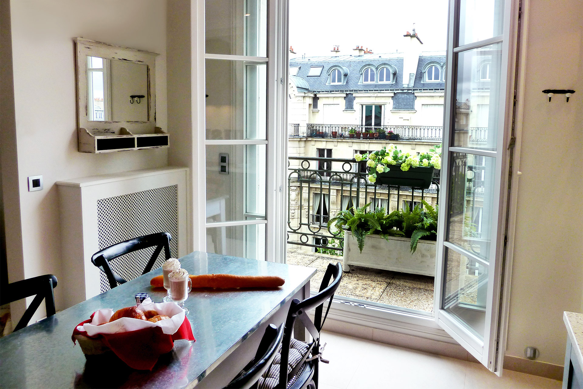 Kitchen opens out onto the large balcony of the Margaux vacation rental offered by Paris Perfect