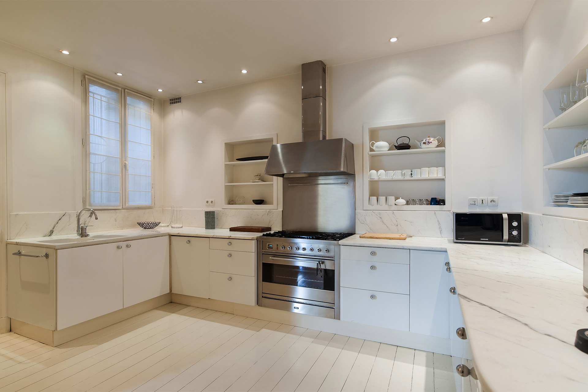 Large kitchen opens directly onto the round breakfast nook in the Cavailles Paris Perfect rental