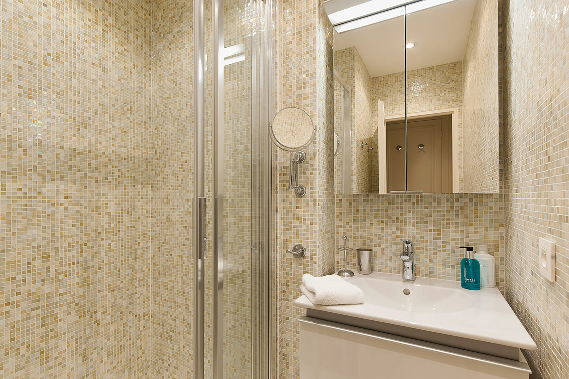 Renovated spacious bathroom with enclosed shower.