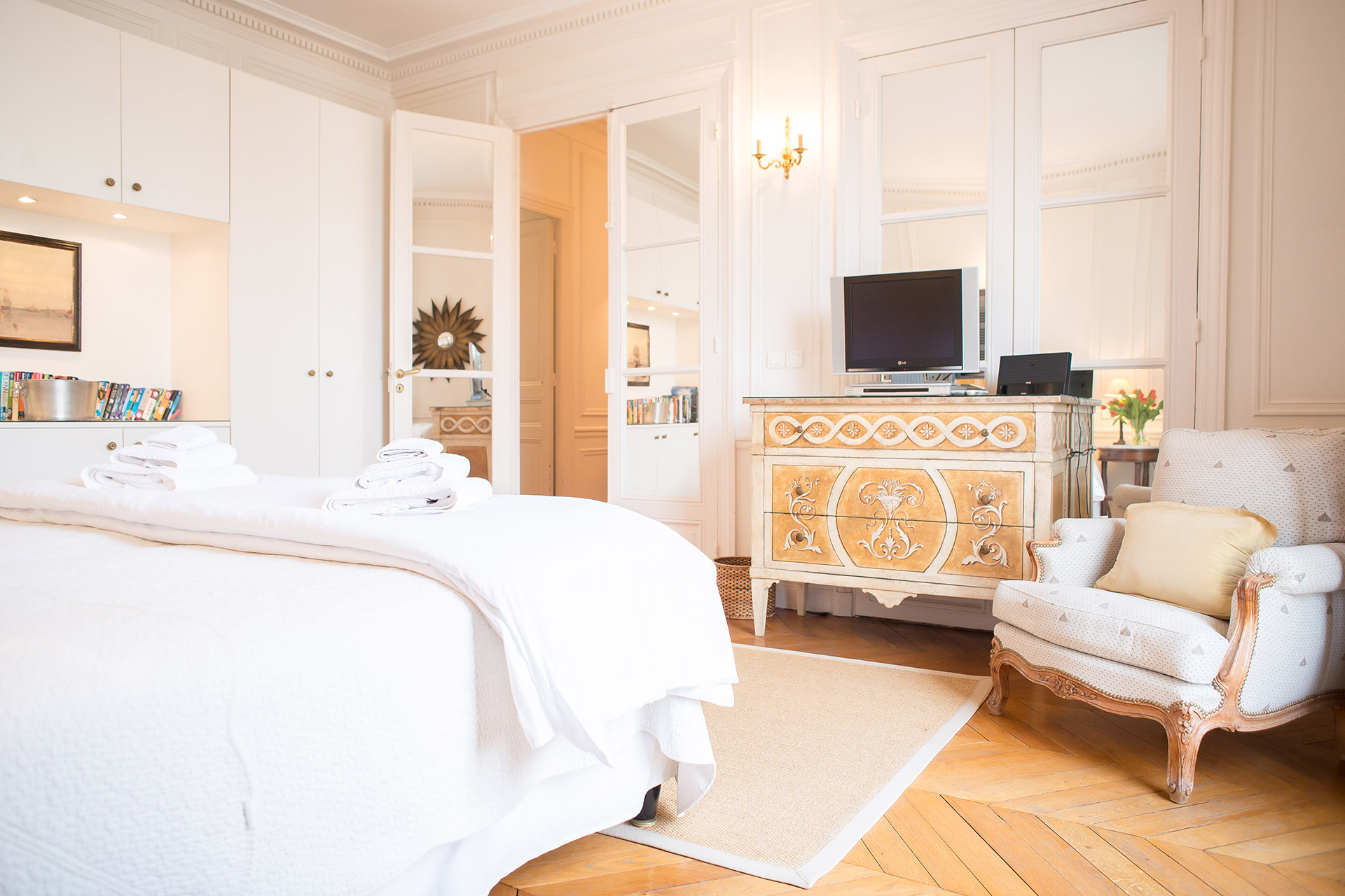 Oversized French door brightens the first bedroom of the Chateauneuf vacation rental offered by Paris Perfect