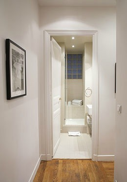 Corridor leads from kitchen toward first bathroom of the Chateauneuf vacation rental offered by Paris Perfect