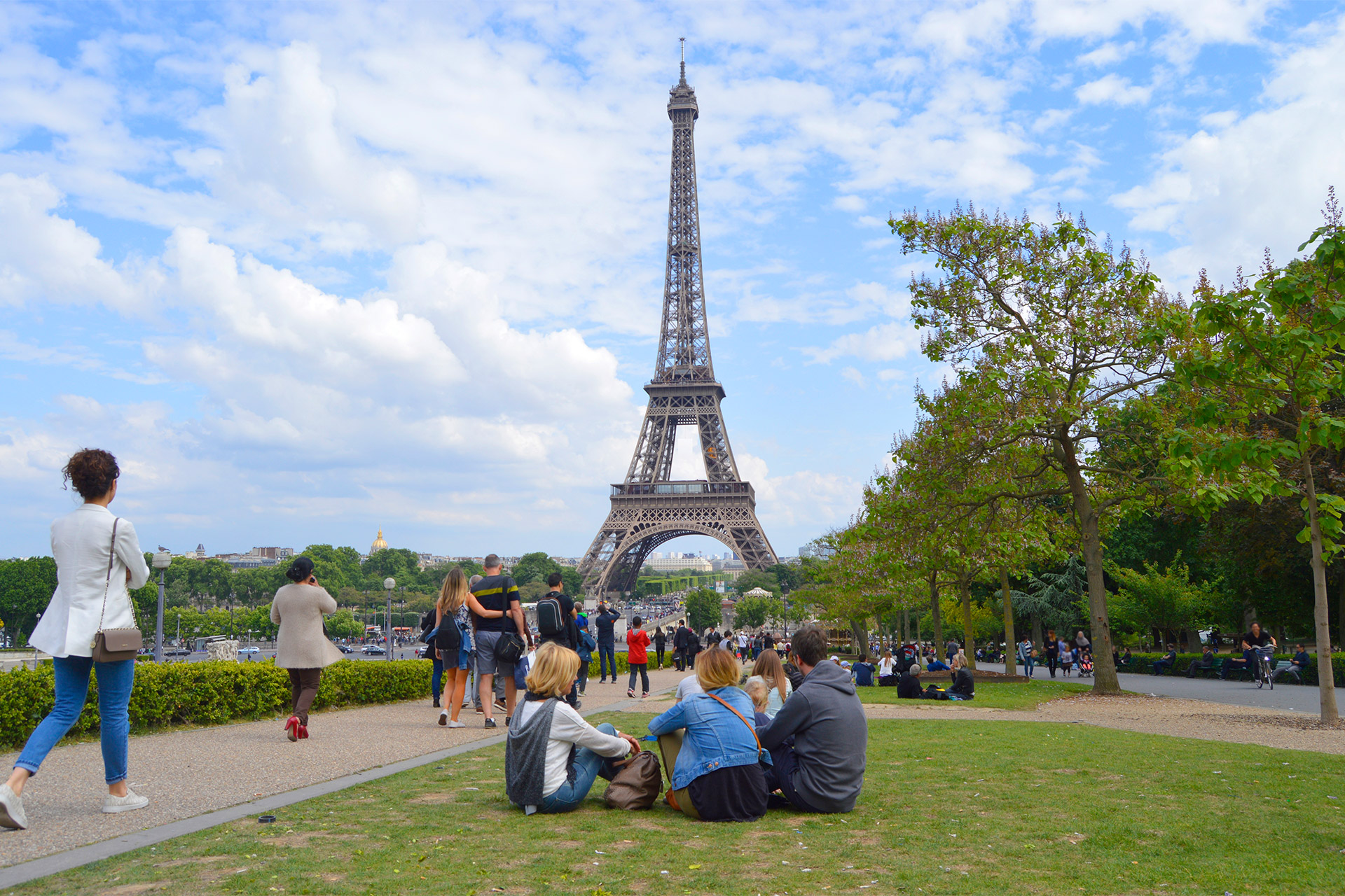 People sitting in Champ de Mars park watching the Eiffel Tower