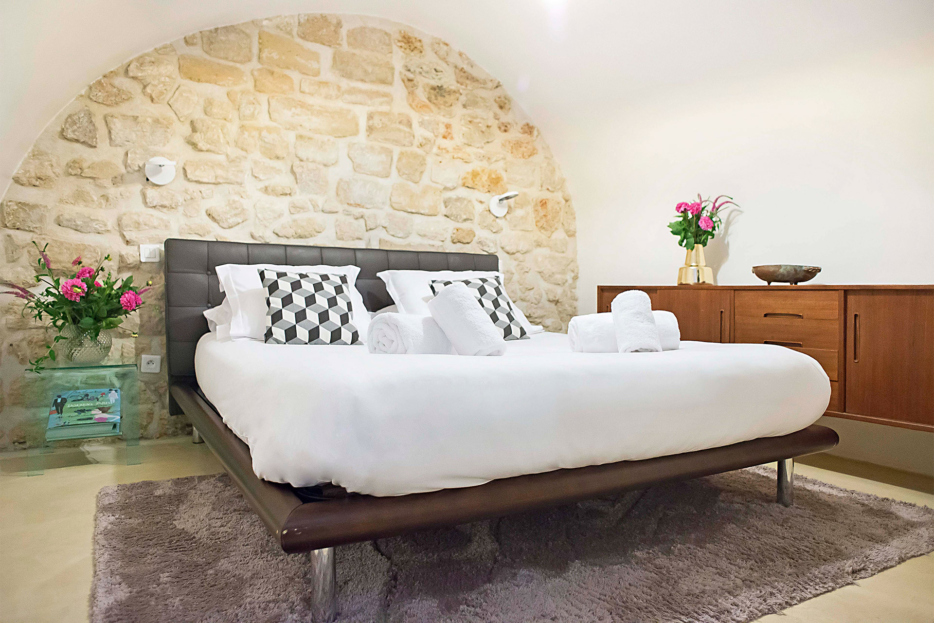 Stunning stone feature wall behind the bed in the Lascombes third bedroom