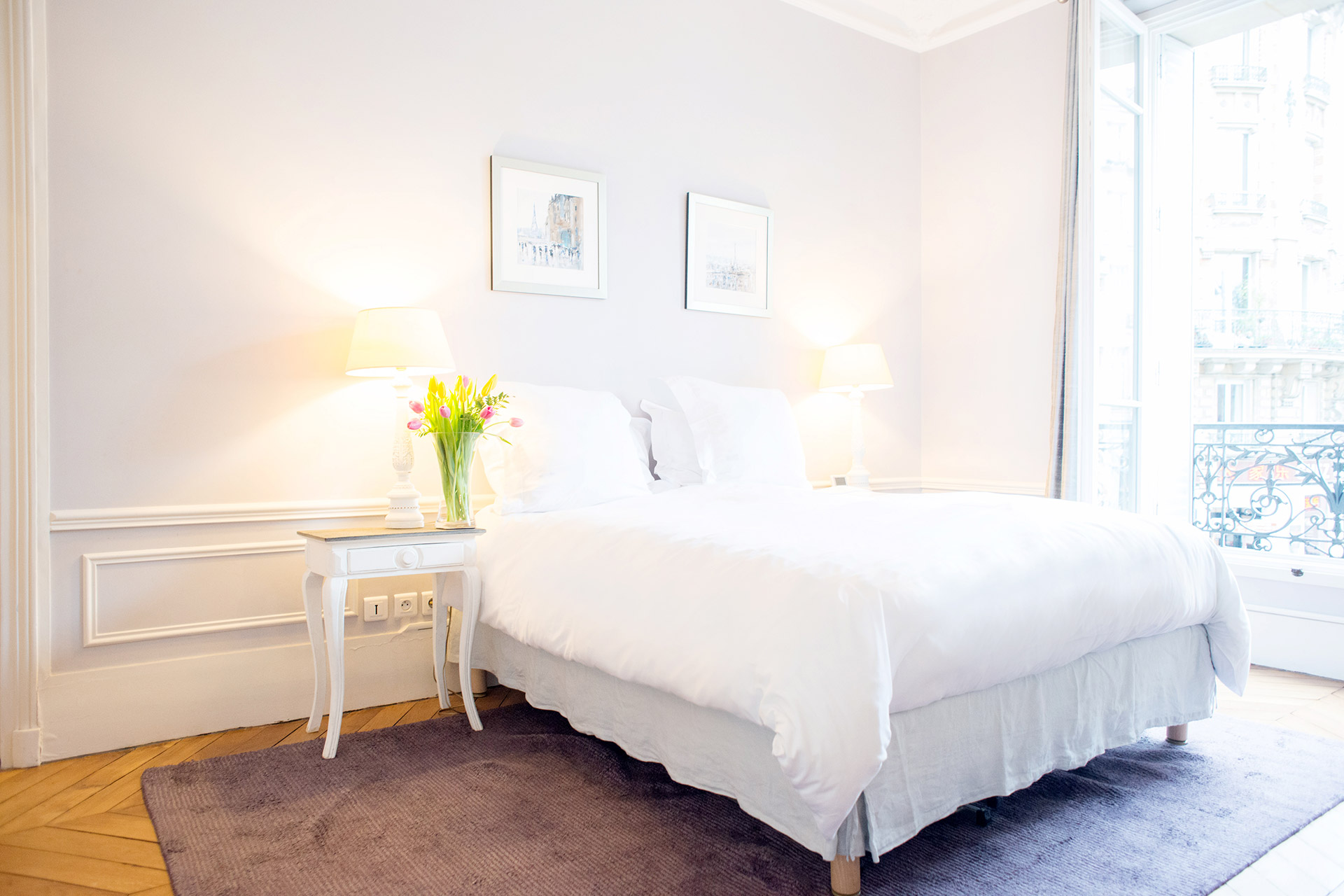 Sunlight streams into the gorgeous master bedroom of the Maubert vacation rental offered by Paris Perfect
