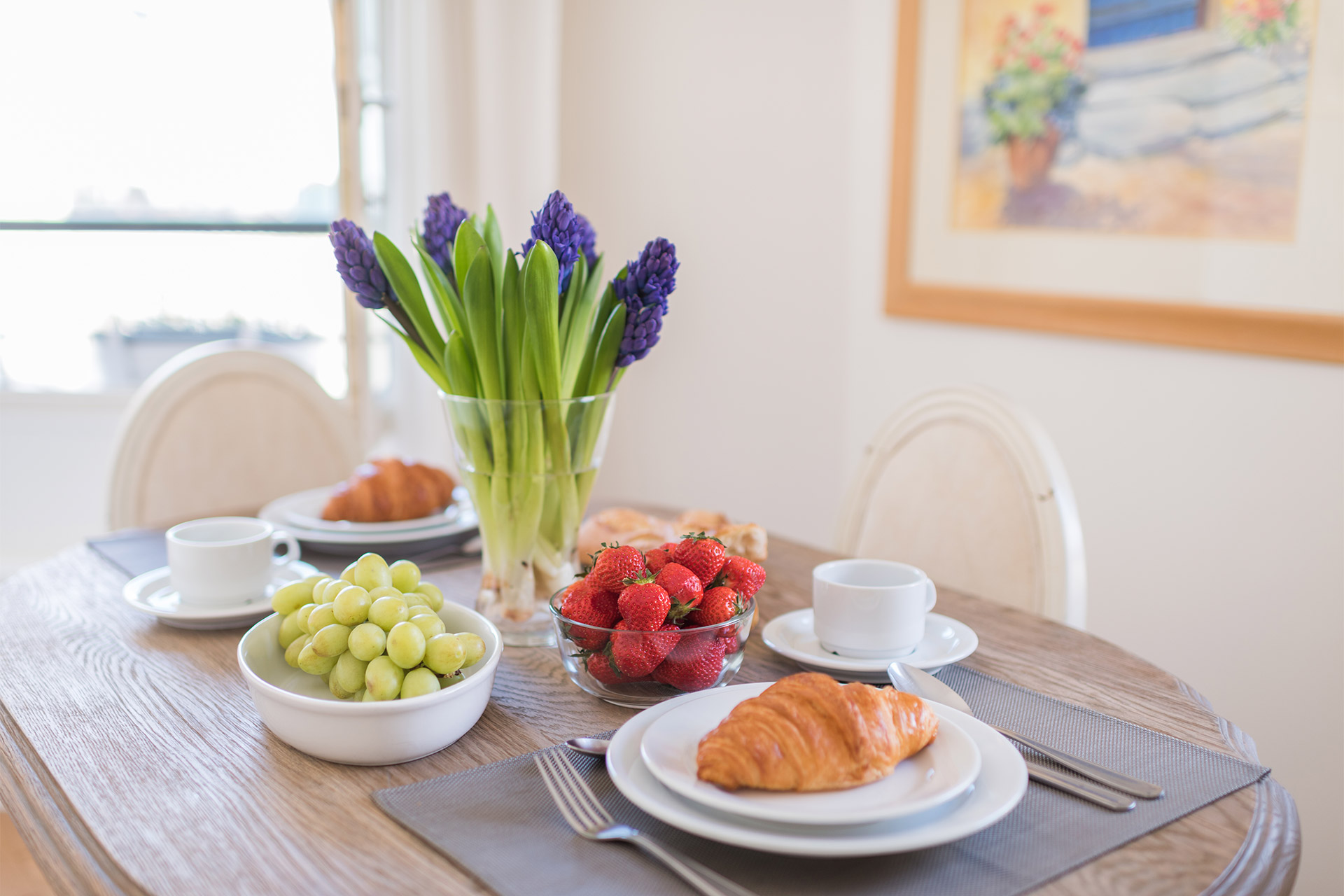 Dining table with fresh fruit and croissants in the Pomerol vacation rental offered by Paris Perfect