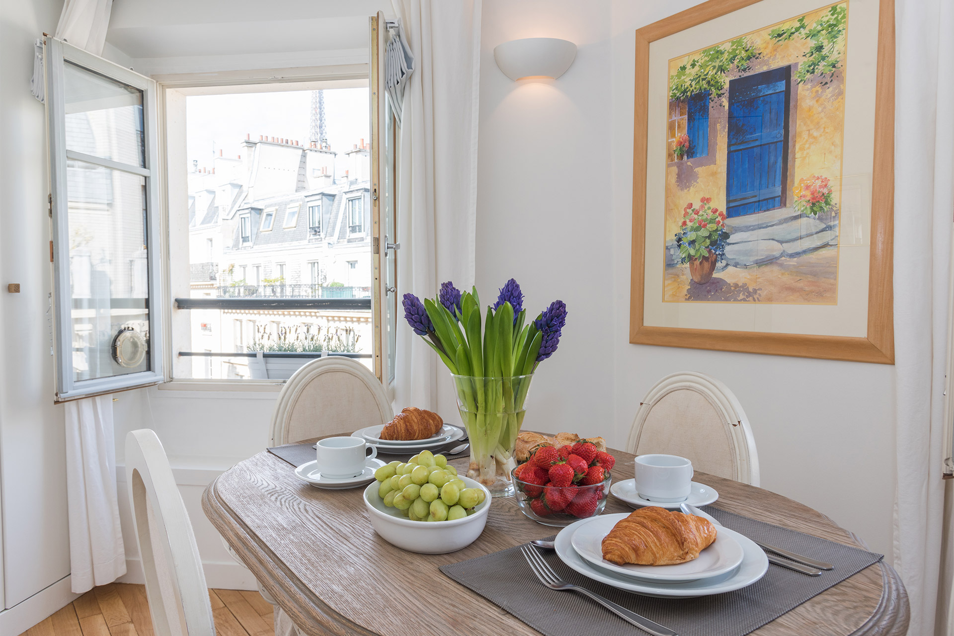 Dining table with a view of the top of the Eiffel Tower in the Pomerol vacation rental offered by Paris Perfect