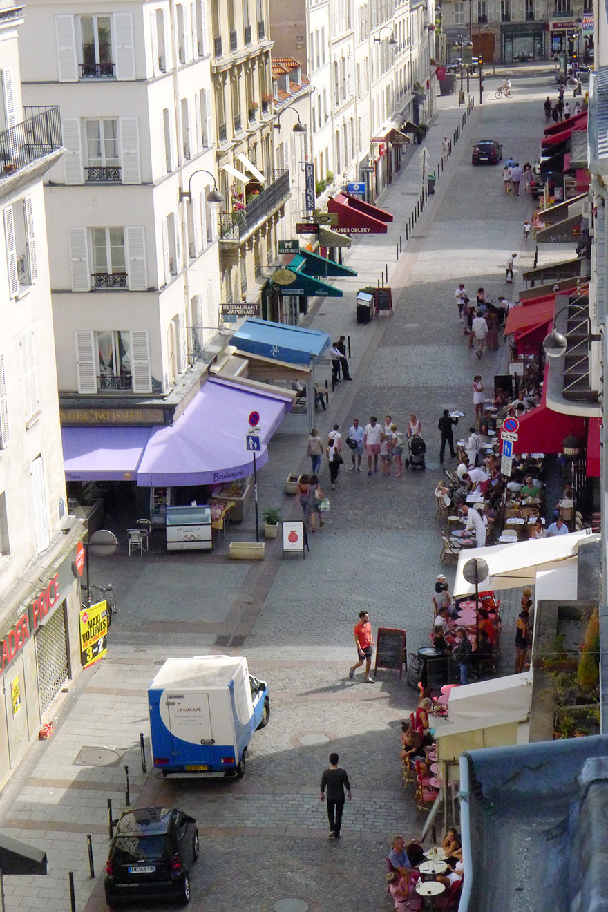 View of the lively rue Cler market street from the Saumur vacation rental offered by Paris Perfect