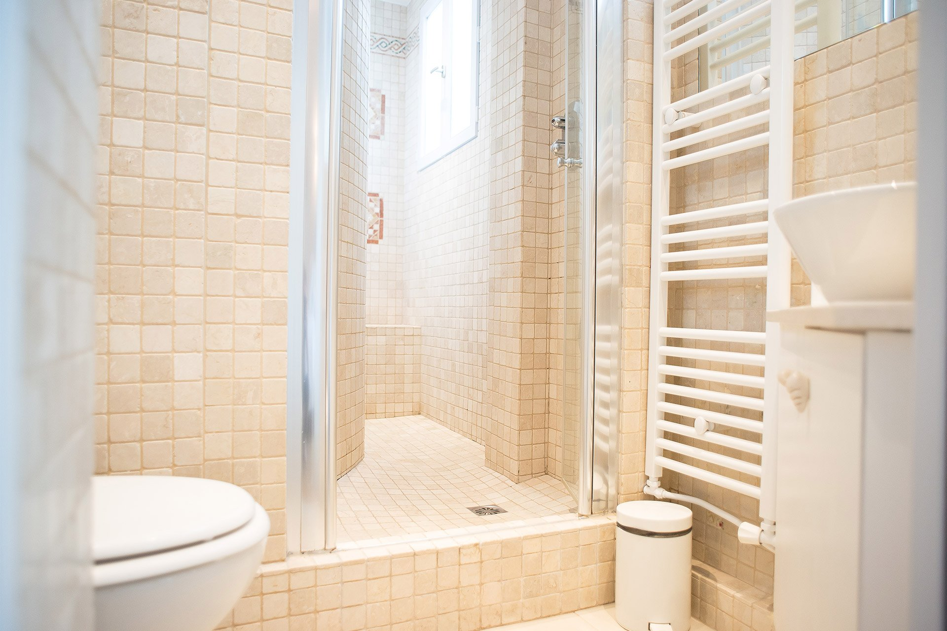 En suite bathroom with shower, toilet and sink in the Saint Emilion vacation rental offered by Paris Perfect