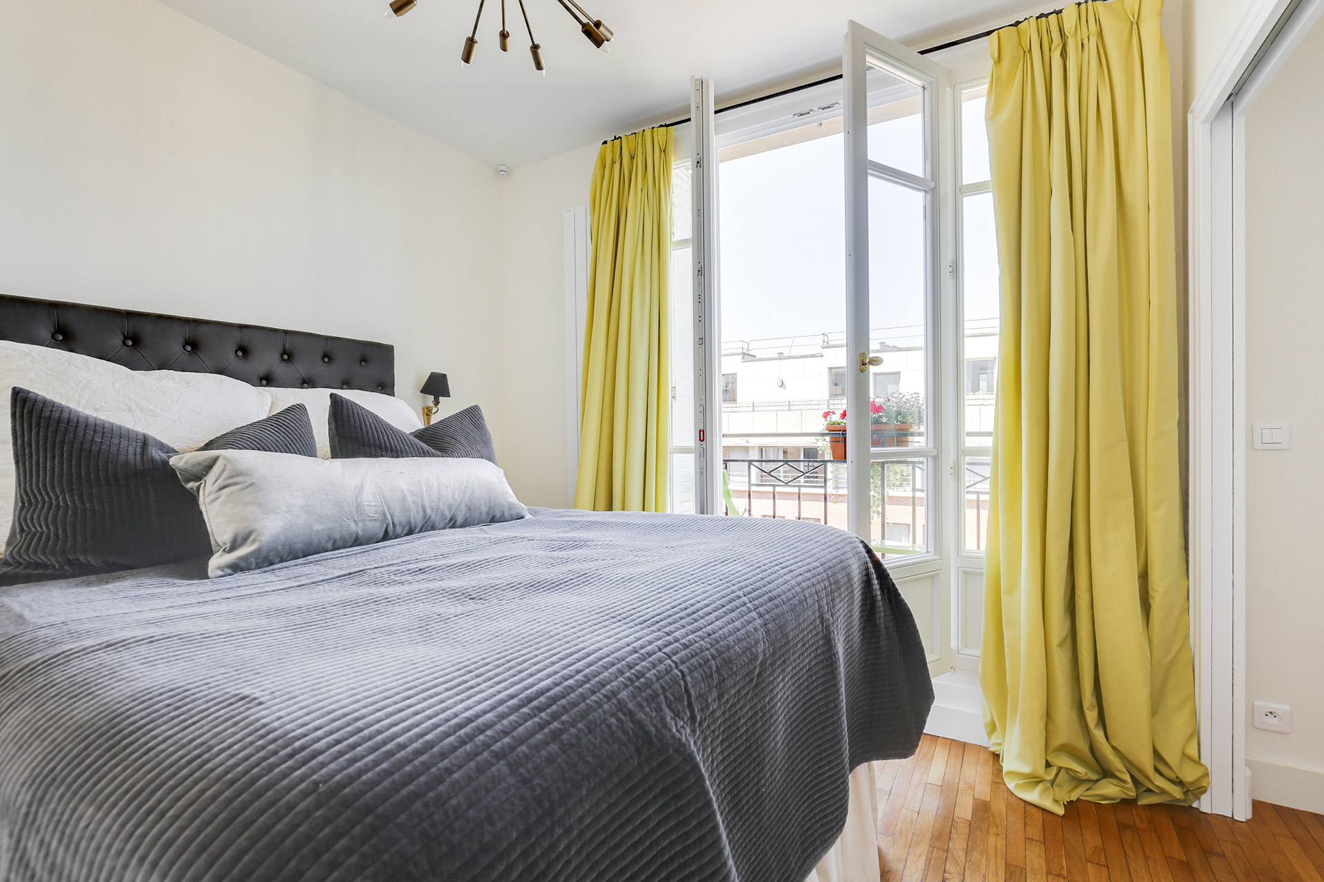 Gaze out over the rooftops from the bed in the morning in the Vivarais vacation rental by Paris Perfect