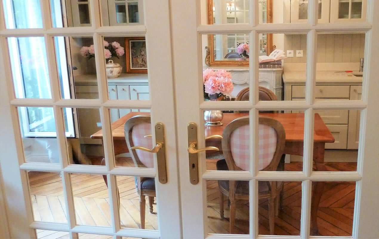 The Provencal kitchen with farmhouse table, taupe velvet dining chairs with pink gingham backs